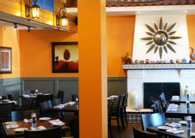 A restaurant with orange walls and lantern style wall sconces