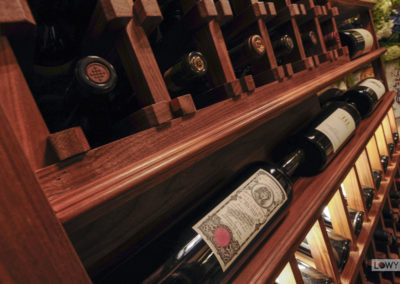 An up-close view of wine bottles in a custom wine cellar