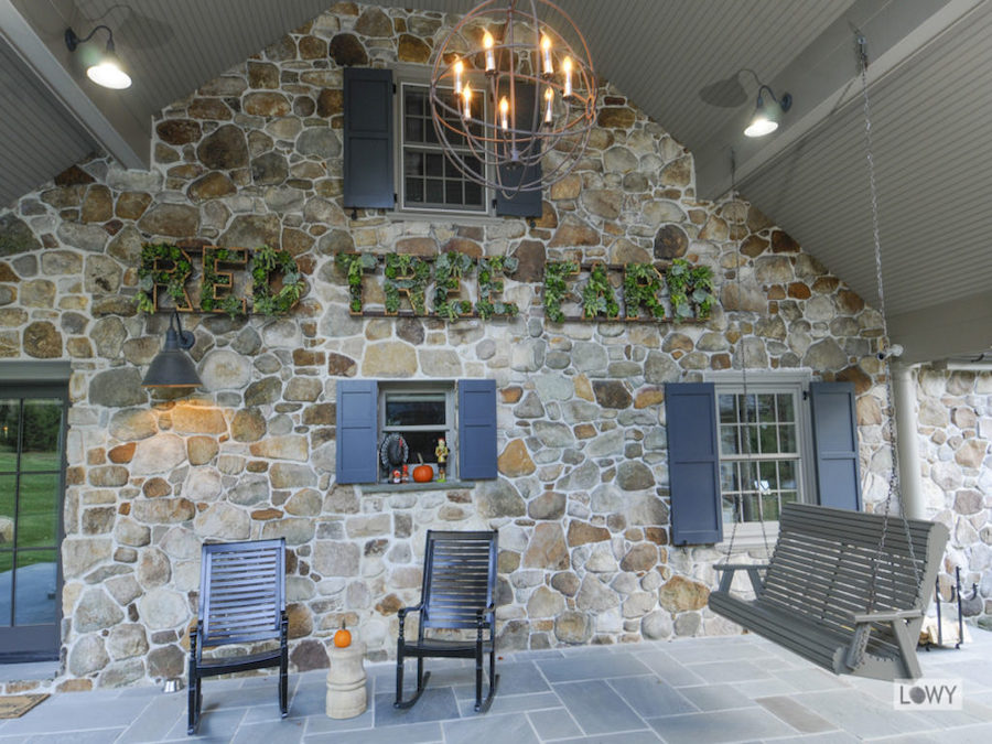 Stone accent wall with rocking chairs in front of it and a swinging bench